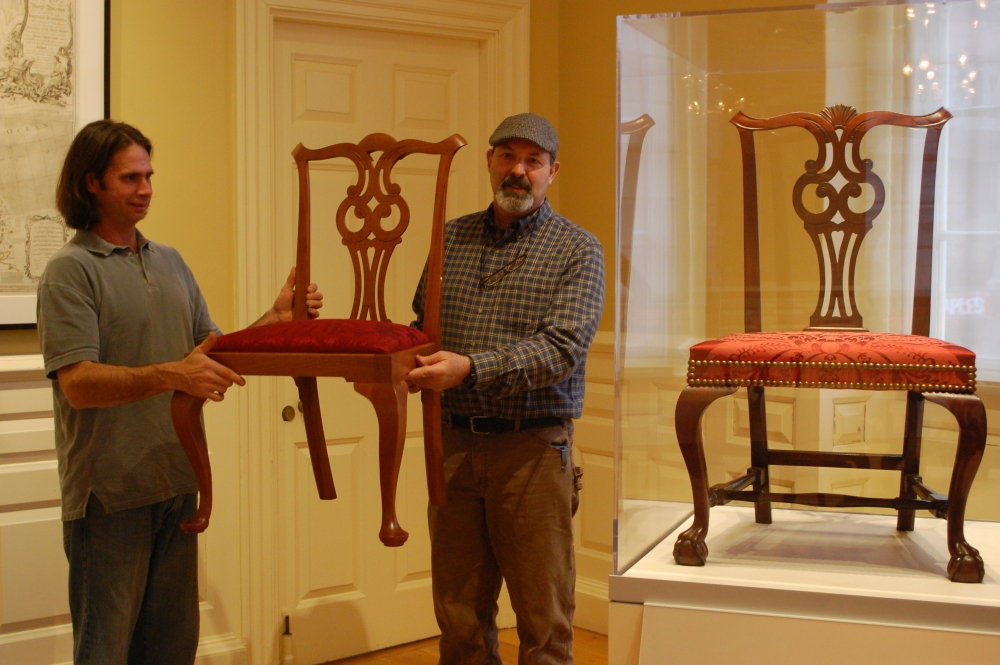 Matt Wajda (left), a 2001 graduate of the NBSS program, holds one of the side chairs he made for the Council Chamber project next to a chair from the collection. (Photo courtesy of the Bostonian Society)