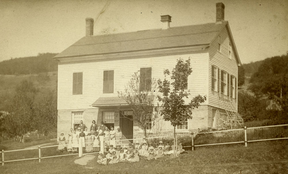 The Shaker schoolhouse with students seated in front. Courtesy, The Winterthur Library, The Edward Deming Andrews Memorial Shaker Collection.